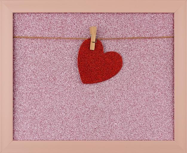 Coração de papel brilhante vermelho pendurado em uma corda em uma moldura rosa