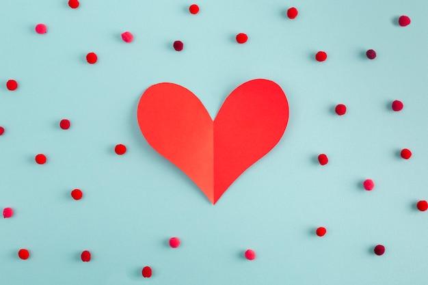Coração de papel entre confete decorativo