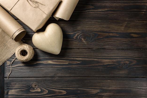 Coração de papel machê, papel artesanal, linho de aniagem e um novelo de barbante em uma mesa de madeira tosca