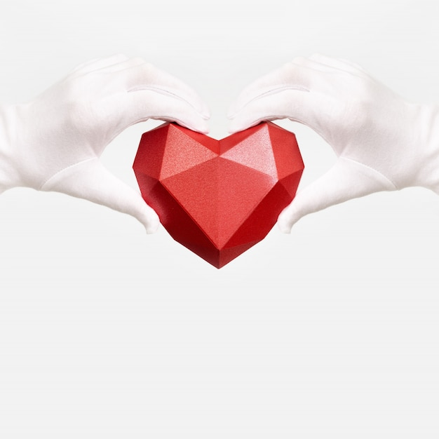 Coração de papel poligonal vermelho nas mãos com luvas de tecido branco sobre fundo branco.