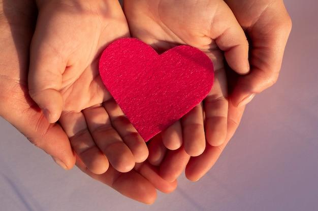 Coração de papel rosa nas palmas das mãos da criança e feminino, vista superior conceito de família do dia das mães do amor