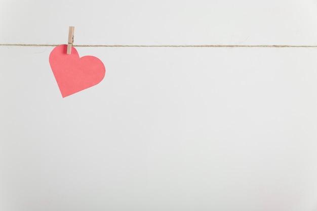 Coração de papel solitário pendurado na corda