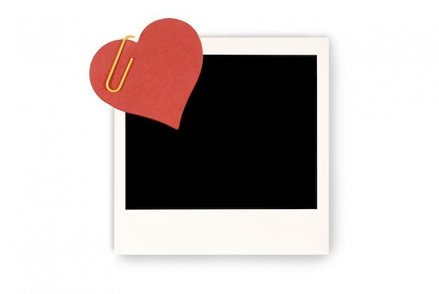 Coração de papel vermelho anexado a uma foto instantânea de polaroid em branco