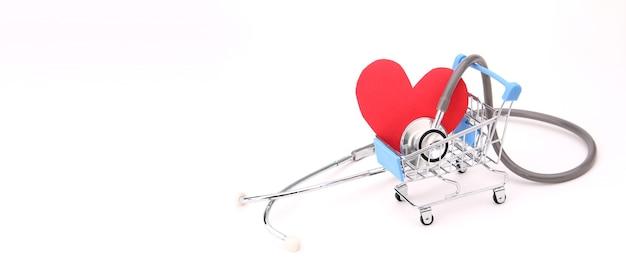 Coração de papel vermelho com estetoscópio no carrinho de compras