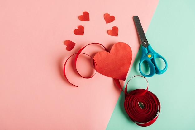 Coração de papel vermelho com uma tesoura