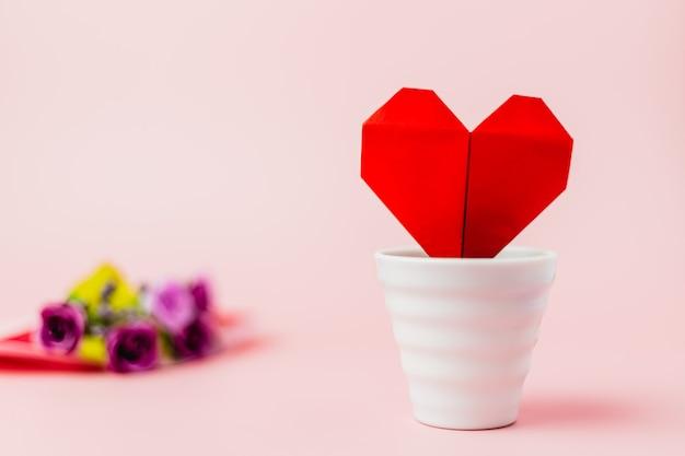 Coração de papel vermelho em vaso de flores brancas com buquê de rosa roxa borrado em fundo rosa para o conceito de amor e dia dos namorados