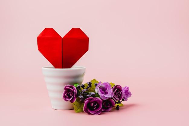 Coração de papel vermelho em vaso de flores brancas com buquê de rosa roxa em fundo rosa para o amor e o conceito de dia dos namorados