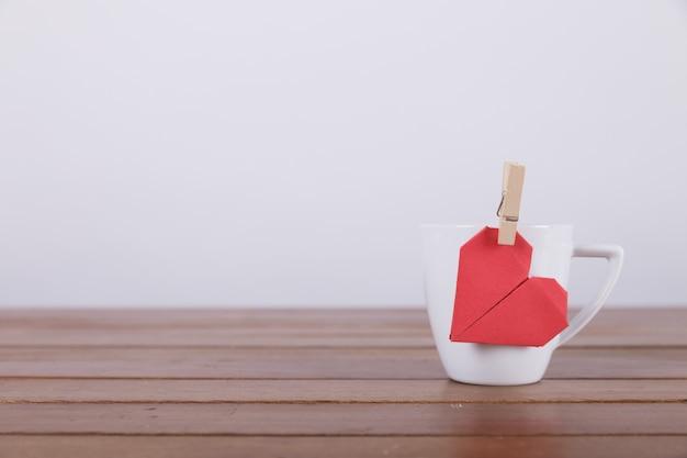 Coração de papel vermelho na caneca