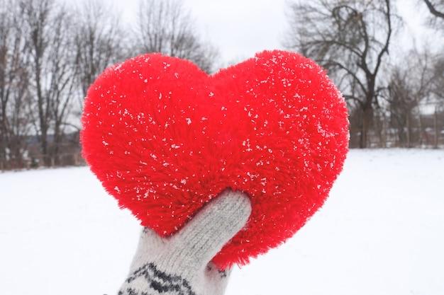 Coração de pelúcia na mão no fundo de uma paisagem de inverno. dia dos namorados e conceito de amor