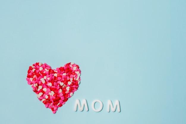 Coração de pequenas decorações perto da palavra mãe