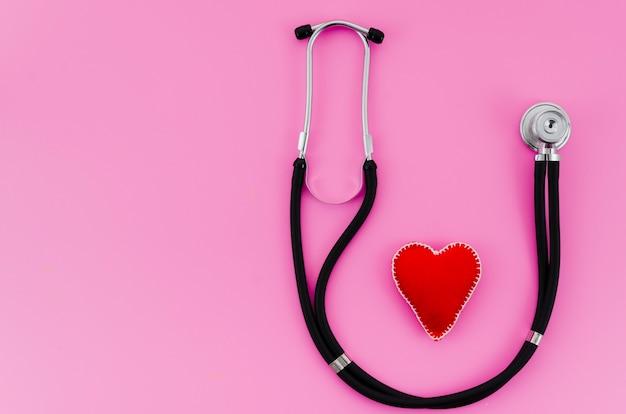 Coração de ponto têxtil vermelho com estetoscópio no fundo rosa