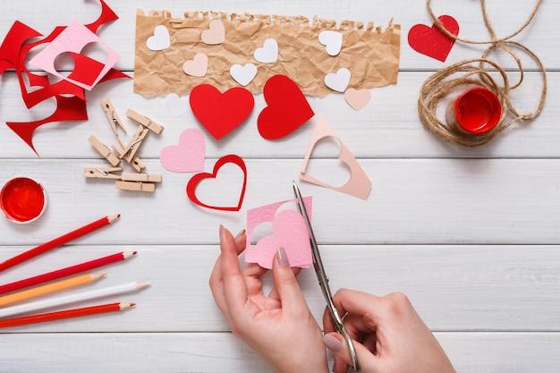 Coração de saudação de presente feito à mão criando, recortando e colando, papel artesanal e ferramentas diy em madeira branca