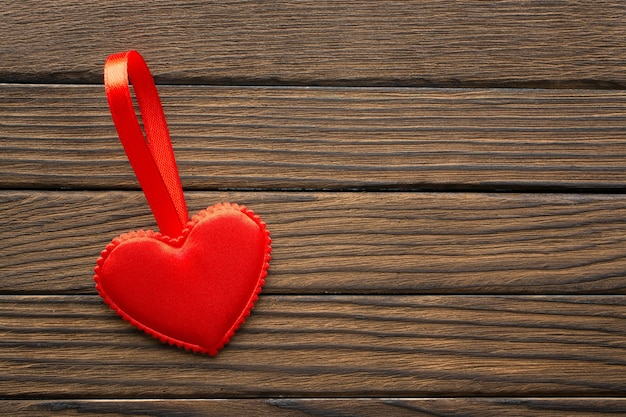 Coração de tecido vermelho com fita em fundo de madeira