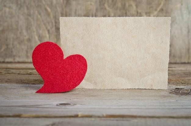 Coração de tecido vermelho com folha de papel em pé sobre uma placa de madeira na mesa de madeira
