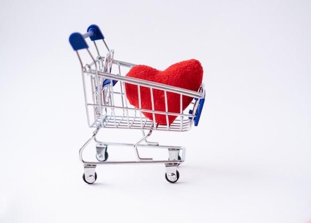 Coração de tecido vermelho no carrinho de compras. compras do dia dos namorados.