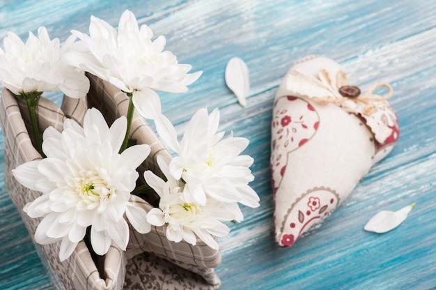 Coração de têxteis e buquê de flores em saco de linho bruto