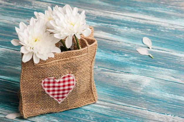 Coração de têxteis e buquê de flores em saco de serapilheira