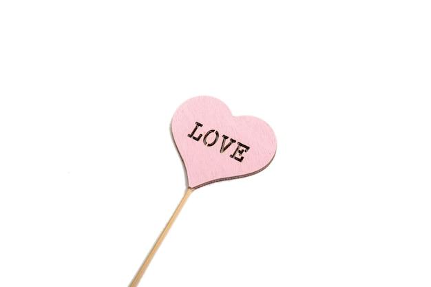 Coração de valentine vermelho de madeira rústico na superfície branca. amor em madeira, conceito de dia dos namorados.