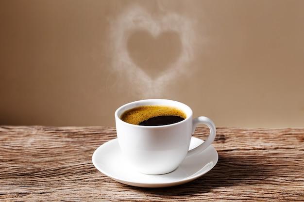 Coração de vapor pairando sobre uma xícara de café vermelha na mesa de madeira com espaço de parede de creme.