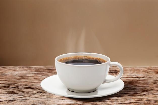 Coração de vapor pairando sobre uma xícara de café vermelha na mesa de madeira com parede creme