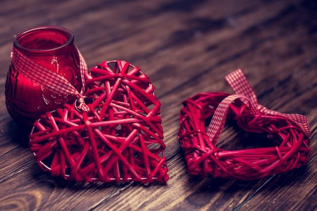 Coração de vime vermelho na mesa de madeira, fundo de romance de vela