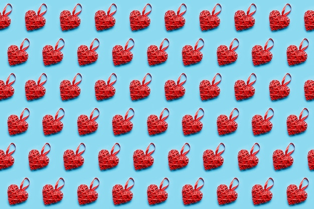 Coração de vime vermelho sobre fundo azul. padrão uniforme. conceito de dia dos namorados, vista superior