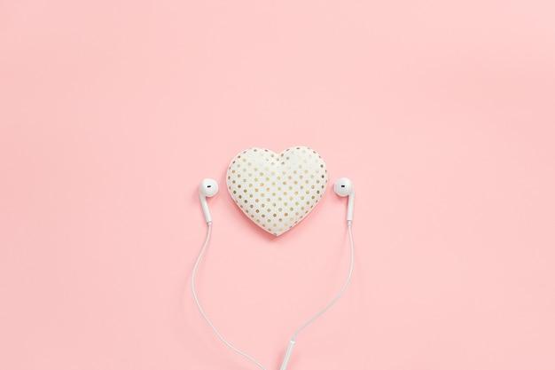 Coração de volume de têxteis decorativos e fones de ouvido brancos sobre fundo rosa
