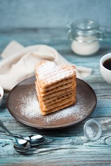 Coração de waffles polvilhado com açúcar de confeiteiro em um prato marrom sobre um fundo cinza-azulado de madeira.