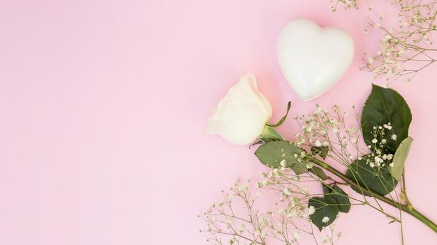 Coração decorativo branco perto de plantas e flores
