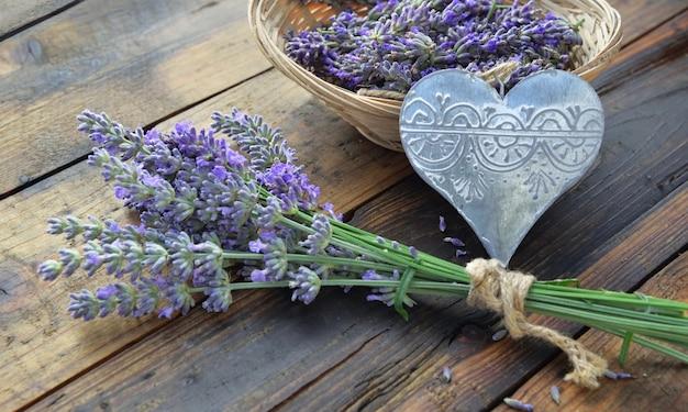 Coração decorativo de metal com um buquê de flores de lavanda na mesa de madeira