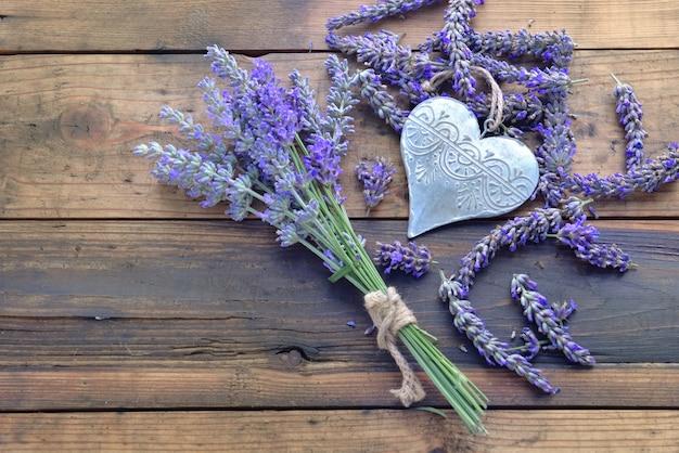 Coração decorativo de metal entre flores de lavanda em fundo de madeira