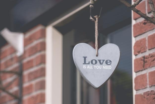 Coração decorativo pendurado na parede de tijolo
