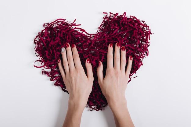 Coração decorativo vermelho e as mãos da mulher com uma manicure