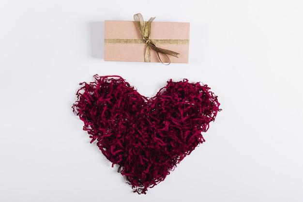 Coração decorativo vermelho e uma caixa com um presente em um fundo branco
