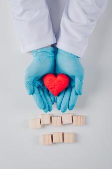 Coração dentro das mãos de um homem com blocos de madeira