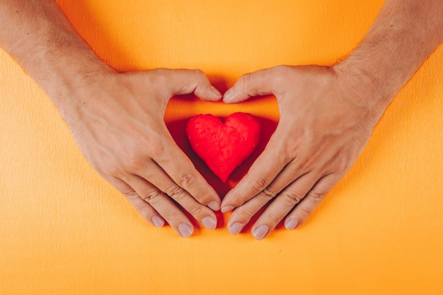 Coração dentro das mãos de um homem na laranja