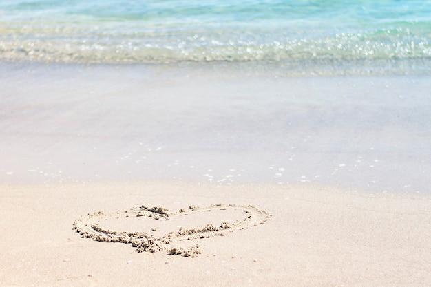 Coração desenhado em uma praia arenosa