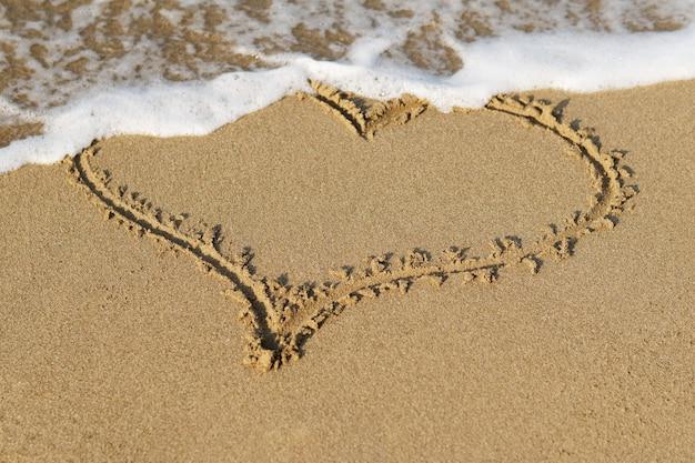 Coração desenhado na areia de uma praia, ondas suaves do mar.