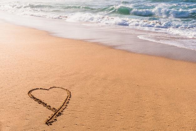 Coração desenhado na areia na praia ao pôr do sol com ondas de lavar em