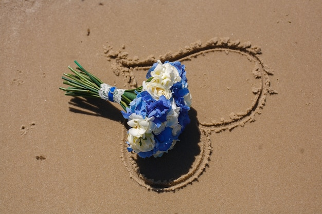Coração desenhado na areia perto com espaço para texto. romântico. bouquet de noiva de flores azuis e brancas na areia. decoração de casamento. conceito de dia dos namorados. conceito de história de amor. detalhes do casamento