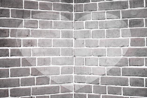 Coração desenhado simétrico no ângulo do close-up da parede de tijolo em escala de cinza.