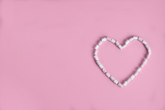 Coração disposta de mini marshmallows rosa sobre um fundo rosa com copyspace