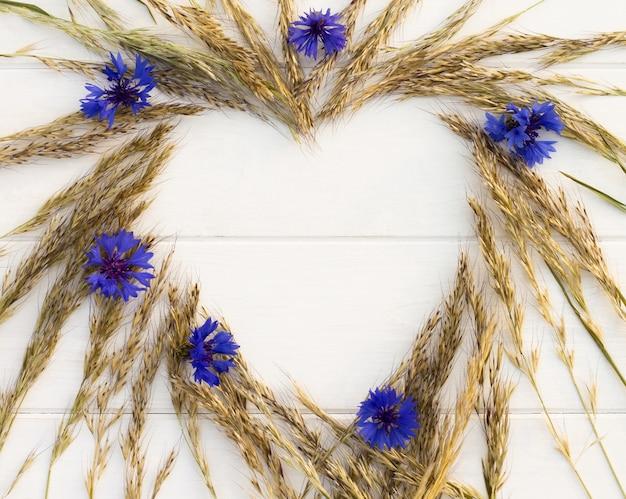 Coração disposto de espigas e flores em um fundo branco de madeira. postura plana. copie o espaço.