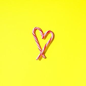 Coração do bastão de doces do natal no fundo amarelo com espaço da cópia. vista do topo. amor, conceito de dia dos namorados. ano novo e cartão de natal