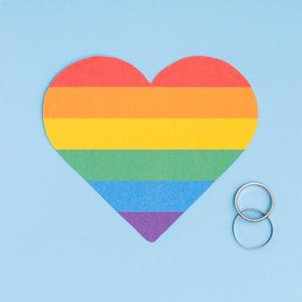 Coração do lgbt do arco-íris e alianças de casamento no fundo azul