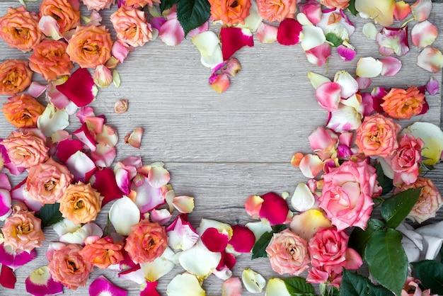 Coração do quadro feito de flores cor-de-rosa no fundo de madeira para o dia de valentim.