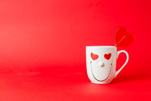 Coração doce vermelho em forma de pirulito em uma caneca com uma carinha sorridente