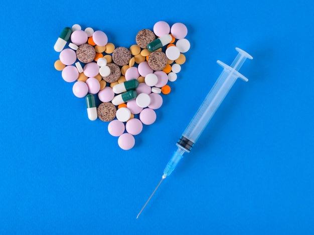 Coração dos comprimidos e da seringa com a agulha no fundo azul.