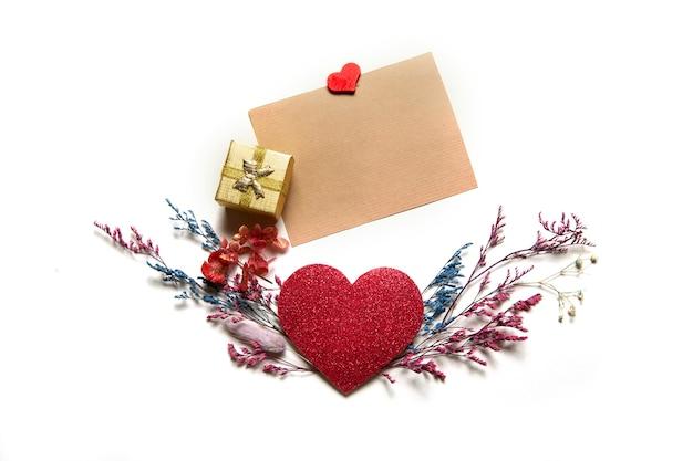 Coração dos namorados vermelho com flores secas multicoloridas e cartão para texto em um fundo branco.