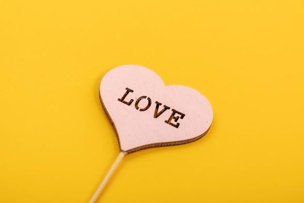 Coração dos namorados vermelho de madeira rústica sobre fundo amarelo. amor em madeira, conceito de dia dos namorados.